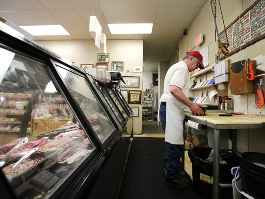 David Krogman, a meat cutter with Jacobs Meat Market, gets ready to put brats in the meat case.