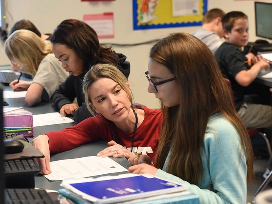 Math teacher Carrie Koch works with student Cecilia Lemas at Wellington Middle School on Tuesday, March 22, 2016. The classroom was the main computer lab but the math class moved in because of space limitations.