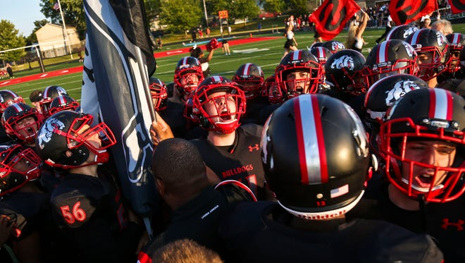 The New Albany Bulldogs football team gets fired up before the season opener against Providence Friday night. The Bulldogs would go on to win 34-0 over the visiting Pioneers, the team's first shutout since 2013 and first win under new coach Steve Cooley.