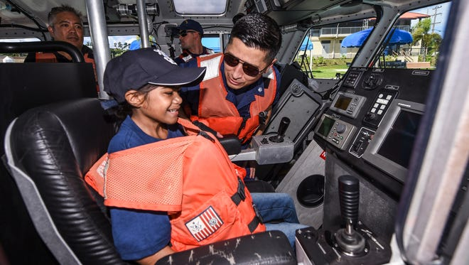 Make-A-Wish Guam and CNMI recipient Maegan Ernis, 11, chats with U.S. Coast Guard Sector Guam Deputy Commander, Cmdr. James Campbell, as she is seated in the pilots chair of a 45-foot Response Boat Medium at the Naval Base Guam in Sumay on Saturday, Sept. 30, 2017. Ernis, who was celebrated as a Sailor for a Day at the Naval Base Guam in Sumay, was diagnosed in 2015 with Fanconi Anemia, a rare genetic disorder, in the category of inherited bone marrow failure syndromes.