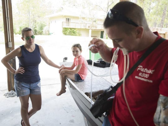 Naples resident and well-known swamp buggy driver Tyler Johns adjusts his med-vac as his wife, Sam, and daughter, Rorie, 6, look on at his home Saturday in Naples. Johns lost his arm in an airboat accident only two weeks ago on May 8, 2016. The swamp buggy community has rallied together to help pay off the families medical bills. Despite his circumstances Tyler is incredibly positive about the whole experience and grateful for the overwhelming support. 'What else can you do. I always look forward,' Tyler said. 'I couldn't ask for better friends.' (Luke Franke/Staff)