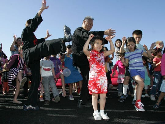 DAVID YAMAMOTO/SPECIAL TO THE STAR Ella Levin (front), next to Sabrina Bell tries tai chi in an audience participation lesson led by David Chang (center back) from the Oak Park Tai Chi Club during Saturday's Chinese New Year celebration at the Camarillo Public Library.