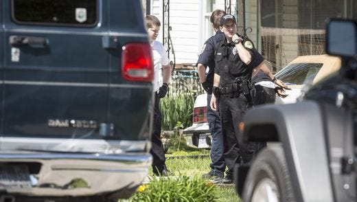 Police watch the scene of three heroin-related arrests May 6, 2016, on North Turner Street in Muncie, Indiana. One of the suspects was shot — not fatally — by an officer, who was also injured when he was thrown from the fleeing van.
