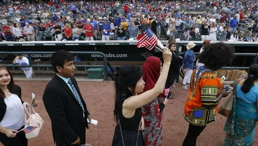 In Sun Lim of Clive waves her flags Monday, July 4, 2016, as she and a group of new citizens leave the ball field following the annual naturalization ceremony at Principal Park before the Iowa Cubs game in Des Moines.