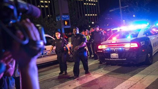 Bystanders stand near police barricades following the sniper shooting in Dallas.