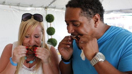 Michelle Bain and Demetrius Booker eat BBQ at the 18th annual Blues, Brews & BBQ festival held at the Louisville Water Tower. Held over three days, the event offers regional BBQ, live music and craft beers tastings. July 10, 2015