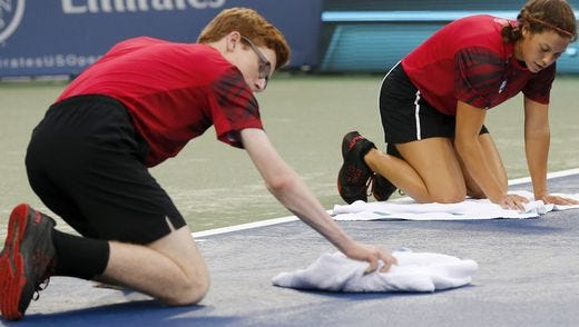 Ball kids and other volunteers helped dry Center Court multiple times during the Western & Southern Open. More than six inches of rain fell throughout the week at the Lindner Family Tennis Center in Mason.