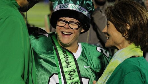 Novi senior Robby Heil shares a laugh with his mother Debby after being crowned homecoming king Friday.