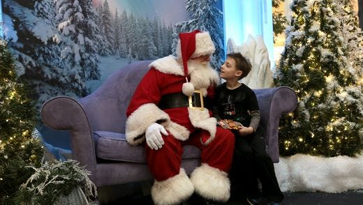 Silas Catlett, 8, of Howell meets with Santa on Sunday, November 29, 2015. This was Catlett's first time seeing Santa.