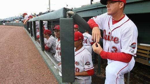 Greenville Drive manager Darren Fenster looks on from the dugout before the team's opening game earlier this month.