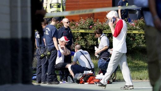 A person is treated by emergency workers as members of the Republican congressional baseball team look on following a shooting in Alexandria, Va 14 June 14, 2017. The Republican House majority whip Steve Scalise and at least four others have been shot at a congressional baseball game practice session, according to media reports