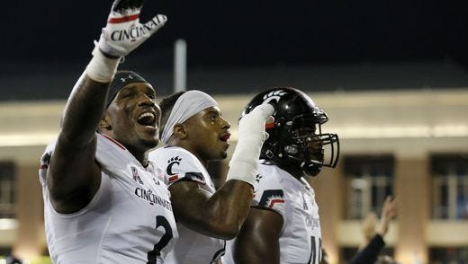 University of Cincinnati players wave goodbye to the Miami student section after Saturday night's 21-17 UC victory.