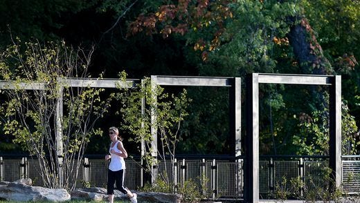 A runner jogs past a new overlook along the Harpeth River at Bicentennial Park in downtown Franklin Wednesday morning, Oct. 5, 2016. The overlook is part of the 3rd Avenue North trail/greenway project.