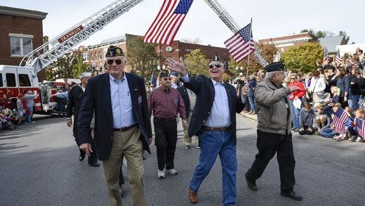 Dennis Anglin, center, reacts as he sees friends in the crowd as he and his fellow veterans march in the Veterans Day Parade on Friday, Nov. 11, 2016, in Franklin, Tenn.
