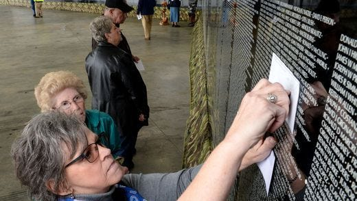 """Janice Holbrook, left, Assistant Director for the Oconee County Veterans Affairs Office, rubs a name for Mildred Brewer, right, of Pickens County, one of 12 names she got for others from the """"The Moving Wall"""" half-size replica of the Washington, DC Vietnam Veterans Memorial on display at the Blue Ridge Electric Cooperative building in Westminster."""