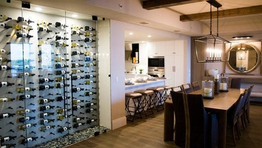 Distinctive design touches at AQUA at Pelican Isle's coastal model by Renee Gaddis Interior Designs include a glass wine closet by the entry and a butler's pantry in a nook in the kitchen.