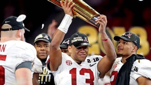 Alabama Crimson Tide quarterback Tua Tagovailoa (13) celebrates with the championship trophy after beating the Georgia Bulldogs.