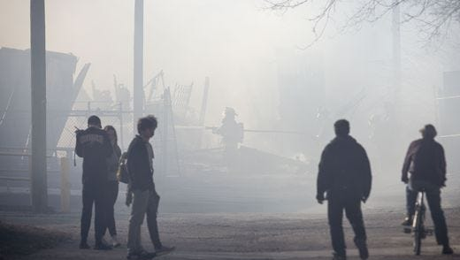Spectators look on as firefighters battle a warehouse fire in the 900 block of South Mound Street on Jan. 28.