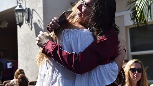 Friends embrace prior to a vigil for the victims of a Florida high school shooting.