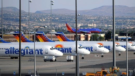 A Southwest airplane lands next to a row of Allegiant Air jets at McCarran International Airport in Las Vegas.