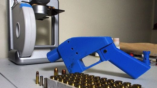 A Liberator pistol appears next to the 3D printer on which its components were made in Hanover, Maryland in this 2013 file photo. ROBERT MACPHERSON/AFP/GETTY IMAGES