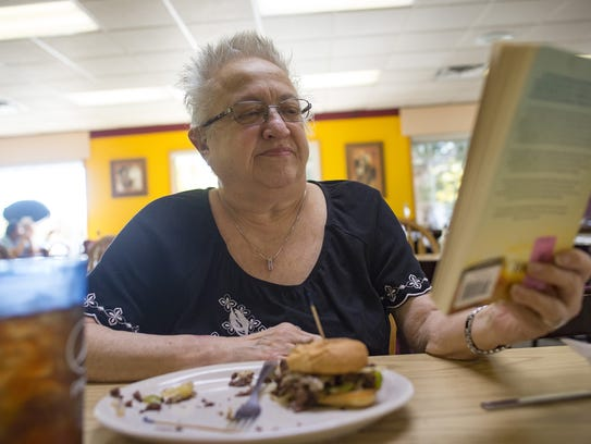 Ann Wenneker reads a book during lunch at Farmer's