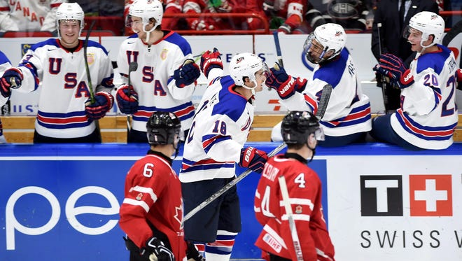 Canada's Brandon Hickey (6) and Haydn Fleury (4) look on as the United States' Colin White (18) celebrates his goal with teammates during second period preliminary hockey action at the IIHF World Junior Championship in Helsinki, Finland on Saturday. Will Borgen, St. Cloud State defenseman, is on the right (20).
