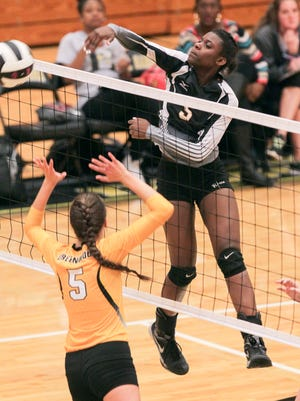 T.L. Hanna's Jodorrian Taylor spikes a ball by Greenwood's Rachel Jolly during the second set at T.L. Hanna High School in Anderson.