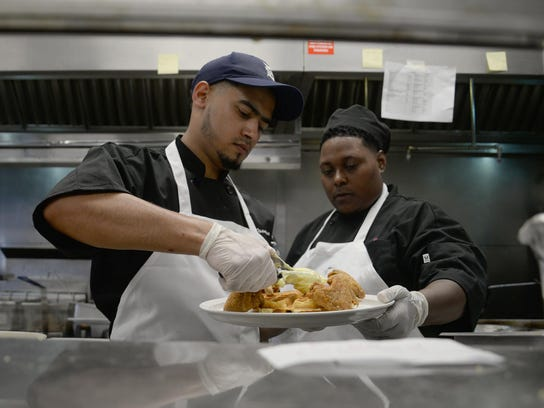 Cooks Ossama Mosleh and Sheamekia Foster prepare a