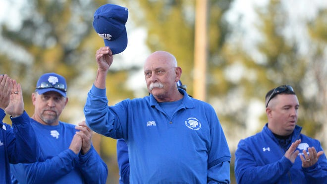 Vic Spotts tips his hat to the crowd Friday night during a ceremony to honor him for the 29 years he spent as Fort Defiance's head baseball coach.
