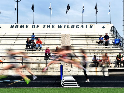 High school athletes compete in the girls'  100-meter