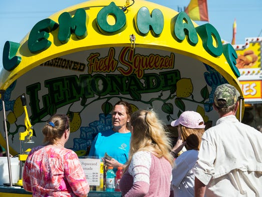 People pick up some lemonade at a vendor during the