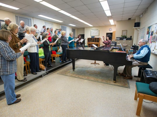 Composer Allen Pote, right, plays the piano during