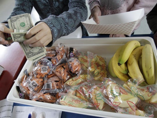 "FILE – In this Dec. 2, 2010, file photo, a child pays for a lunch consisting of fruits and vegetables during a school lunch program at Fairmeadow Elementary School in Palo Alto, Calif. California and Pennsylvania both passed laws in 2017 to outlaw ""lunch shaming"" of children for unpaid meals, with the Pennsylvania measure that became law in November requiring communication about money owed on meal accounts to be done between school officials and parents, and not involve the student. (AP Photo/Paul Sakuma, File)"