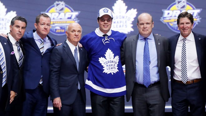 Scottsdale's Auston Matthews celebrates onstage with the Toronto Maple Leafs after being selected No. 1 overall in the 2016 NHL draft on June 24, 2016 in Buffalo, New York.