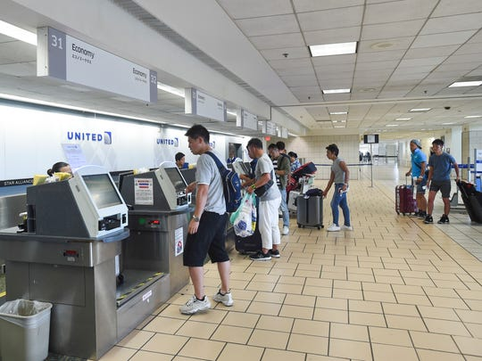 United Airlines passengers check in for their flights at the Antonio B. Won Pat International Airport in this June 25, 2018, file photo.