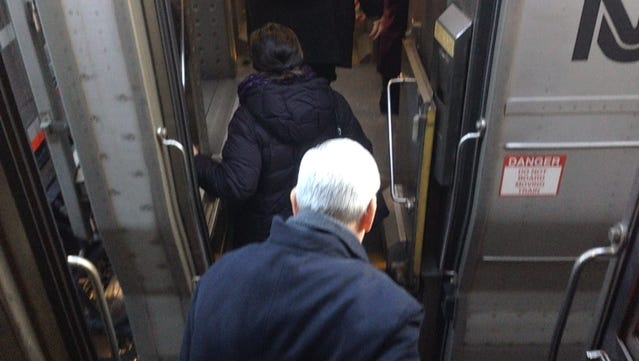 NJ Transit commuters transfer between trains by walking over the backs of seats Tuesday morning in Ramsey, N.J.