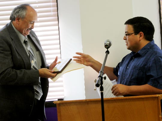 Abe Villarreal, at right, gives Mike Carillo the Martin Luther King Jr. Service Award for the outstanding community service for developing outreach programs for families of the incarcerated. The award was presented on Monday at Western New Mexico University's annual Martin Luther King Jr. ceremony.