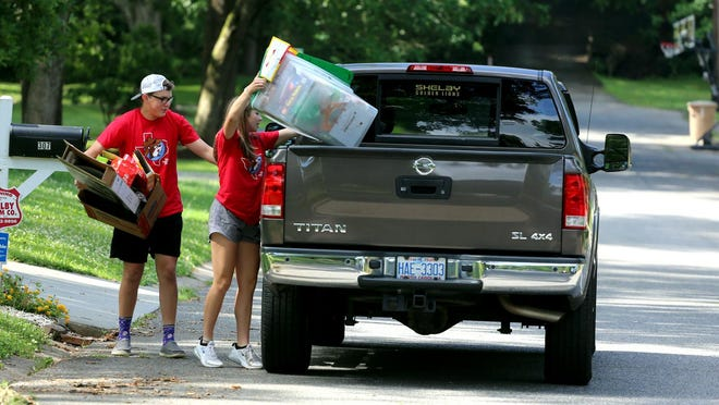 Eli Wilbanks, 16, and Ansley Walker, 15, pick up recycling along Winsdor Drive in Shelby on Friday. The high school students decided to make their own recycle pick up route after Shelby discontinued the service last fall.