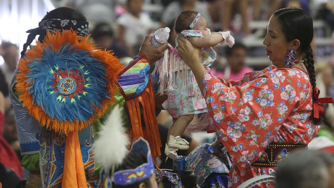 A family readies the outfit of a baby during the Morongo Band of Mission Indians annual Thunder and Lightning Pow Wow in Cabazon on Saturday.