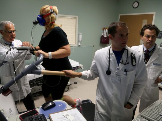 (L to R) Dr. Barry Franklin keeps an eye on Detroit Free Press reporter Kristen Jordan Shamus as exercise philologist Roger Sacks watches a computer monitor with her vitals during a stress test.