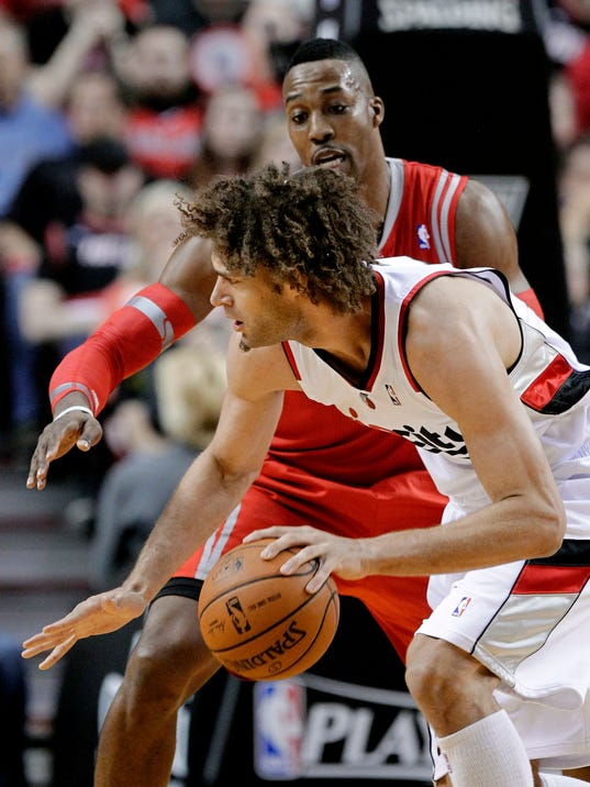 Portland Trail Blazers center Robin Lopez drives on Houston Rockets center Dwight Howard during the first half of Game 3 of an NBA basketball first-round playoff series in Portland, Ore., Friday, April 25, 2014. (AP Photo/Don Ryan)