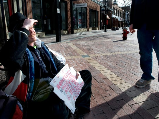Justin Densmore talks with a passerby who stopped to give him a dollar and a cigarette on Church Street in Burlington in February 2012.