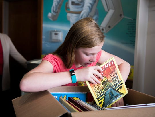 Charlotte Olson, 12, organizes her books Tuesday at