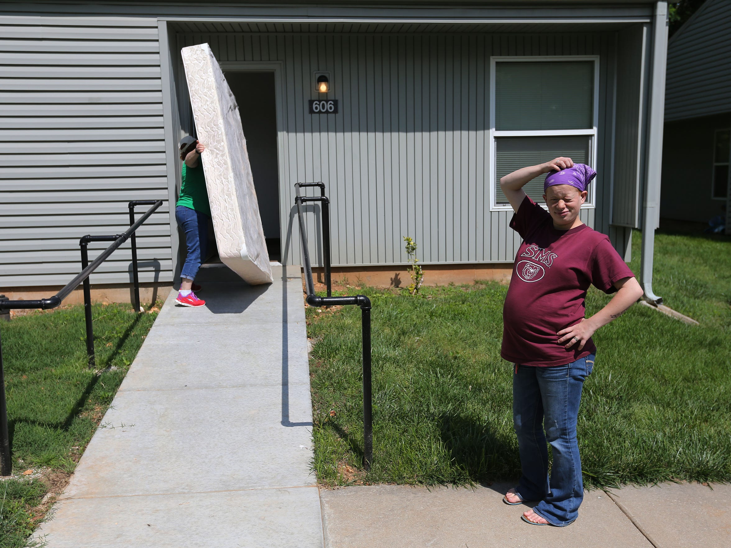 Lyzz Buford's mother carries a mattress into Lyzz's