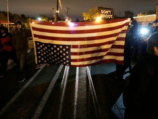 Protesters march with an inverted American flag during a protest near the Ferguson, Mo., police headquarters Friday, Oct. 10, 2014, in Ferguson.  (AP Photo/Charles Rex Arbogast)