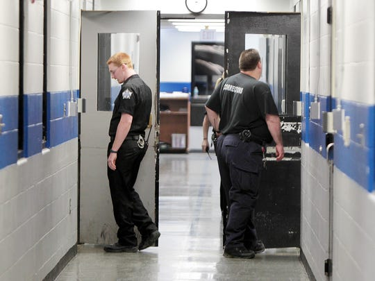 "In this file photo, Grant County Detention Center deputy jailers Jeffrey Sur (left) and Dan Hess conduct a ""watch tour"" in which they check inmates and cells to ensure everything is in order in the facility."