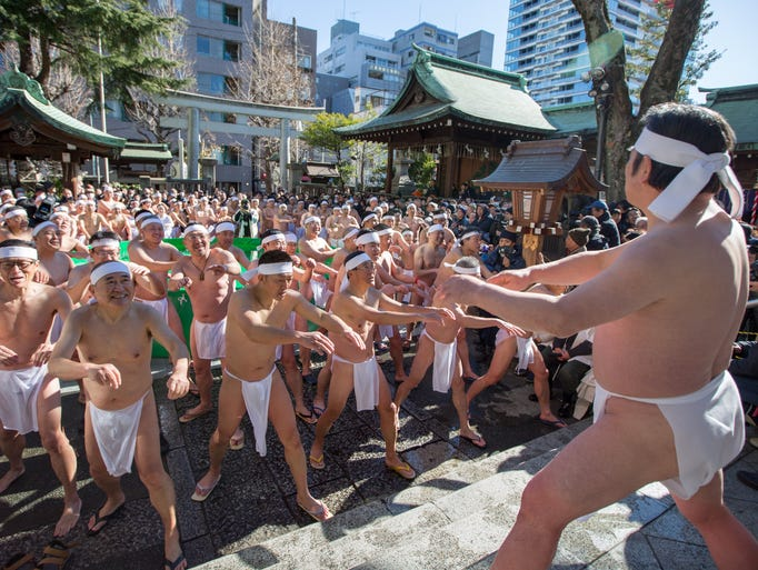 Men wearing only loincloths warm themselves as they