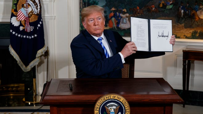 President Trump signs a presidential memorandum on the Iran nuclear deal from the Diplomatic Reception Room of the White House, Tuesday, May 8, 2018, in Washington.