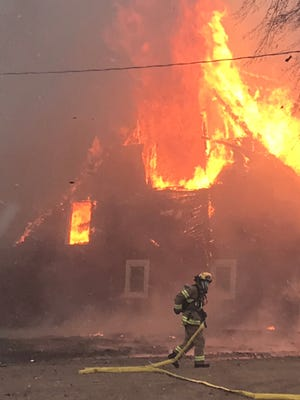 A volunteer firefighter hauls a fire hose in the foreground of the fire consuming the Peterson's historic barn on Nov. 1.